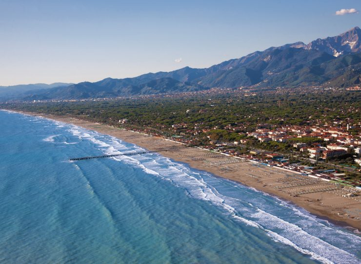 Long range photograph of sea, beach town, and mountains around Forte dei Marmi