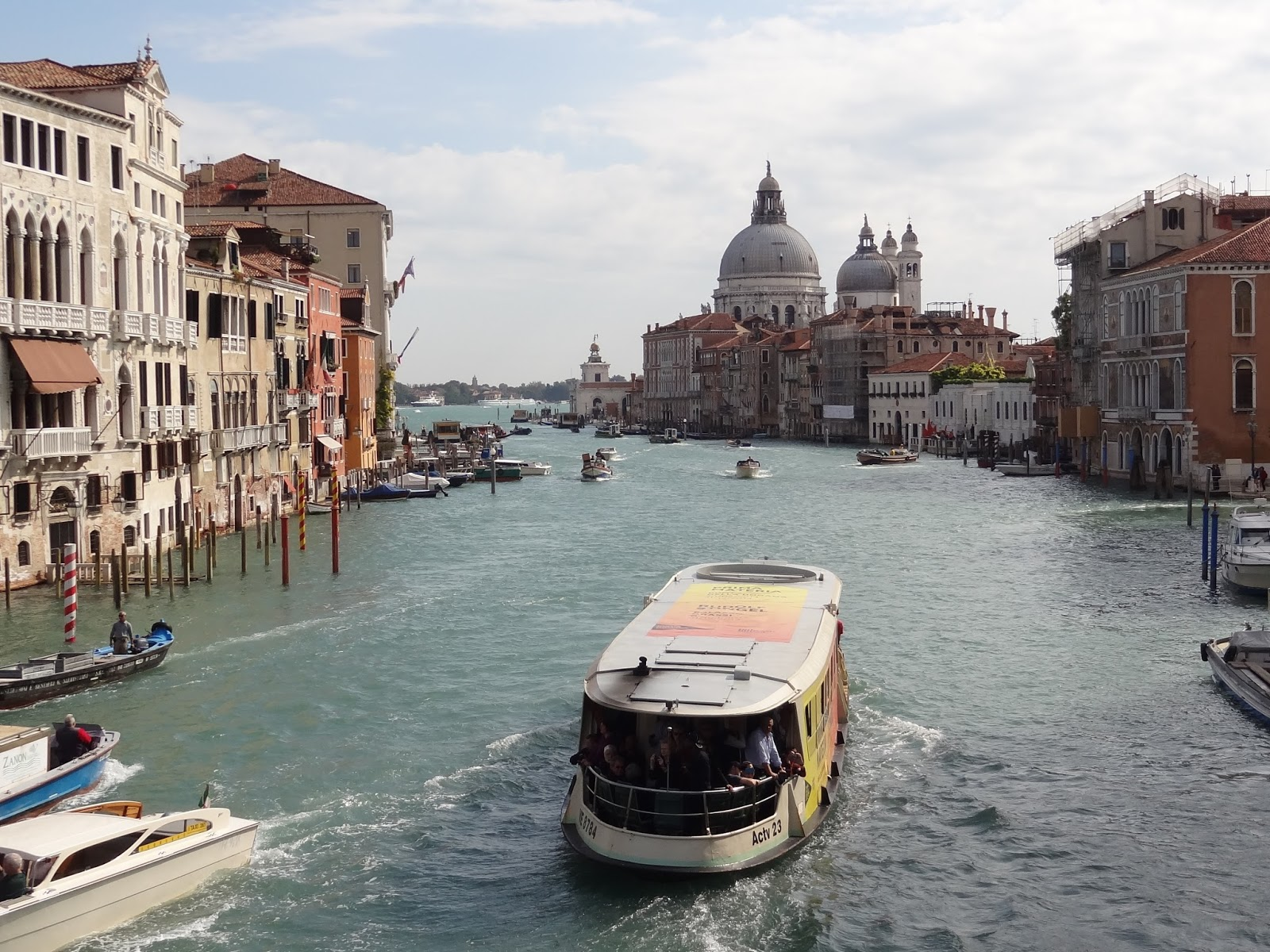 view of Venice Grand canal with large water taxi and St. Mark's Basilica in distances